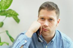 Man watching boring TV show. Handsome unshaved man watching boring TV show at home stock photo