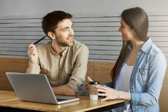Handsome unshaven male freelancer sitting on a meet in cafe, showing project to customer and talking about work details. Stock Photo