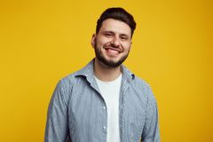 Attractive bearded young man laughing out loud, smiling broadly, showing his white straight teeth against yellow royalty free stock photography