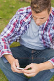 Handsome unsmiling student sitting on grass texting Royalty Free Stock Photo