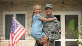 Handsome USA soldier in military uniform holding happy daughter, homecoming. Stock footage stock video