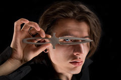 Handsome vampire looking through knife Stock Images