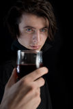Handsome vampire with pale skin and blue eyes. Holding glass of wine or blood, Halloween theme Stock Photos