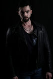 Handsome vampire wearing a black leather jacket. On a black background Royalty Free Stock Photography