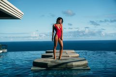Handsome view of girl relaxing at swimming pool with ocean at background. Cute young woman in red bikini posing. Amazing view of girl relaxing at swimming pool stock photography