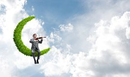 Handsome violinist on moon in blue sky play his melody Stock Photography