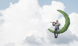 Handsome violinist on moon in blue sky play his melody Royalty Free Stock Images
