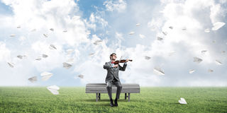 Handsome violinist in park on wooden bench play his melody Stock Photography