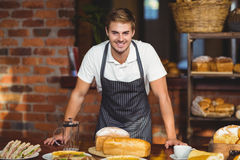 Handsome waiter bended over a food table Royalty Free Stock Photos