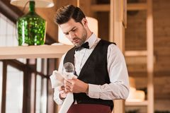Waiter cleaning wineglass Royalty Free Stock Photos