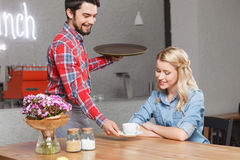 Handsome waiter giving cup of coffee to woman. Serving to you. Young handsome waiter giving cup of coffee to pretty blond-haired woman Stock Image