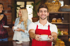 Handsome waiter handing a cup of coffee Royalty Free Stock Photography