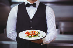 Handsome waiter holding a plate. In a restaurant royalty free stock photography