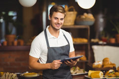 Handsome waiter holding a tablet. Portrait of a handsome waiter holding a tablet at the coffee shop Royalty Free Stock Images