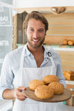 Handsome waiter holding tray of bread rolls Stock Image