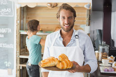 Handsome waiter holding tray of croissants Stock Image