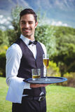 Handsome waiter holding a tray with drinks Stock Photos