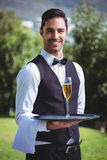 Handsome waiter holding a tray with glass of champagne Stock Images