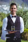 Handsome waiter holding a tray with glass of whiskey. Outside Royalty Free Stock Photo