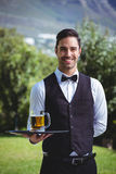 Handsome waiter holding a tray with a pint of beer stock image