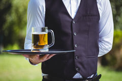 Handsome waiter holding a tray with a pint of beer. Outside Stock Photos