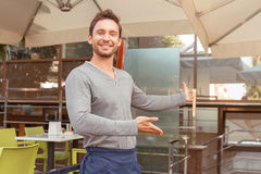 Handsome waiter inviting to cafe Stock Photos