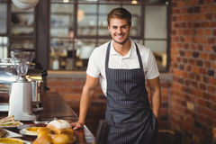 Handsome waiter leaning on a food table Stock Image
