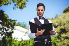 Handsome waiter looking at the menu Stock Image