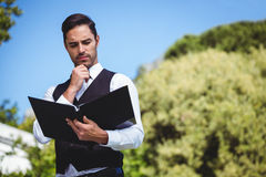 Handsome waiter looking at the menu Royalty Free Stock Photography