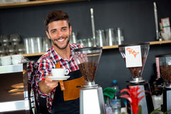 Handsome waiter offering a cup of coffee Stock Photography