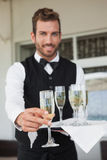 Handsome waiter offering flute of champagne Royalty Free Stock Photo