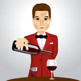 Handsome waiter pouring wine into glass Royalty Free Stock Images