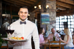 Handsome waiter in a restaurant. Smiling handsome waiter wearing a white shirt and a bowtie holding a tray with food and drinks in a restaurant Stock Image
