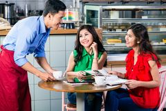 Handsome waiter serving coffee at the table of two beautiful women. Side view of a handsome and polite waiter smiling while serving coffee at the table of two stock photography