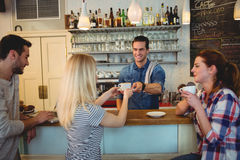 Handsome waiter serving coffee to customer with friends. Handsome waiter serving coffee to young customer with friends at cafeteria Royalty Free Stock Photos