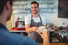 Handsome waiter serving coffee to male customer at cafeteria Stock Image