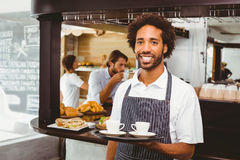 Handsome waiter smiling at camera holding tray Stock Images