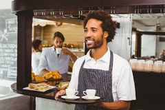 Handsome waiter smiling and holding tray Stock Photography