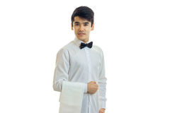 Handsome waiter stands upright keeps on hand towel and looking forward Royalty Free Stock Photos