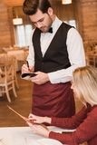 Waiter writing down the order of customer. Handsome Waiter writing down the order of customer at the restaurant Royalty Free Stock Photo