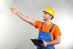 Handsome warehouse worker with clipboard pointing. At something, on light background Stock Photography