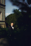 Handsome wealthy confident groom near old mansion background at Stock Photography