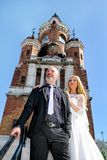 A handsome wedding couple is standing on the stairs in front of the beautiful old church. royalty free stock photo