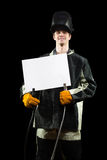 Handsome welder holding a blank form. isolated on. Welder holding a blank form. isolated on black background Stock Image