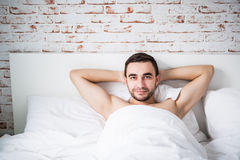 Handsome well built man resting in his bed on brick wall in room at home Stock Images