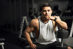 Handsome well built weightlifter sitting thoughtfully Stock Photo