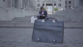 Handsome well-dressed boy sitting on the stairs on the street doing home work at the background. Old purse standing on stock video footage