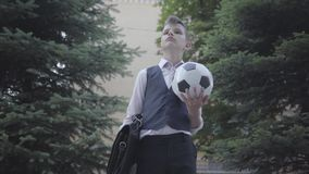 Handsome well-dressed boy standing on the street holding the soccer ball and purse. Serious young man simultaneously stock video footage