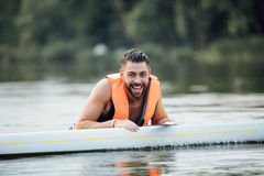Handsome wet man on paddleboard Royalty Free Stock Images