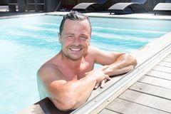 Handsome wet man in swimming pool at resort holidays hotel vacation. Concept Stock Photos